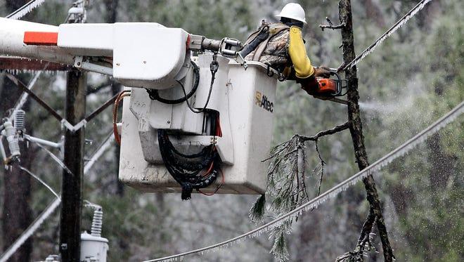 Broken icy branches hang on power lines Wednesday in Summerville, S.C.