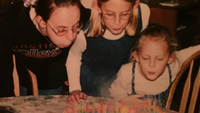 Stephanie Dickrell, 13, Emily Whipple, 9, and Erin Drees, 6 blow out the candles on their joint birthday cake near Plymouth, Wis. in 1999.