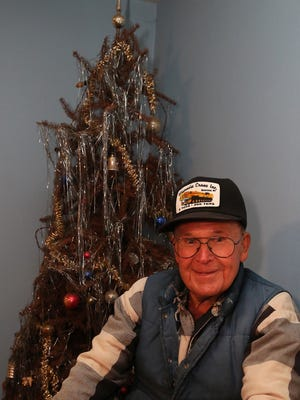 Neil Olson of Wausau sits in front of the natural Christmas tree that has stood in his house since Christmas of 1974. He is waiting until he gets all of sons together to take the tree down. Photo taken, Friday, October 17, 2014.