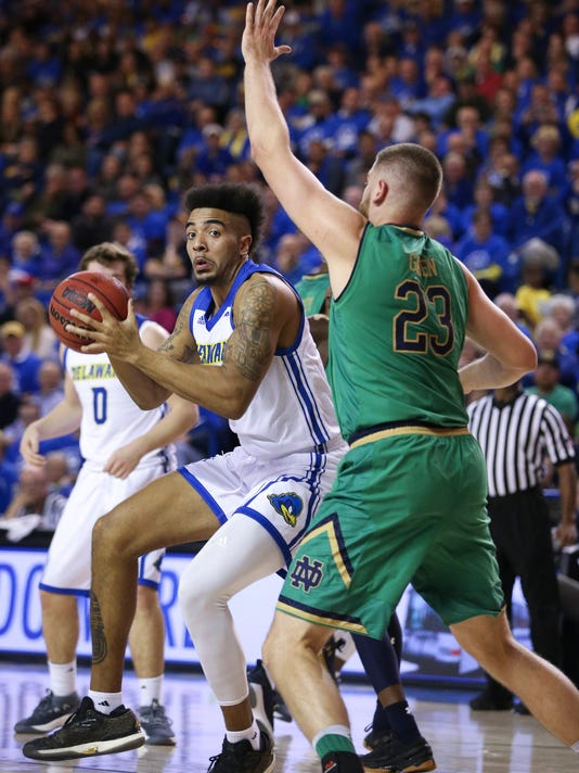 Delaware's Eric Carter tries to work past Notre Dame's Martinis Geben during the first half of an NCAA college basketball game Saturday, Dec. 9, 2017, in Newark, Del. (William Bretzger/The Wilmington News-Journal via AP)