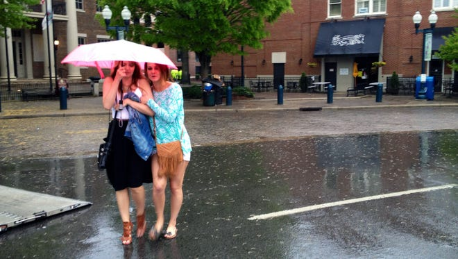 Kelsey Nord and Livi Sholar walk in rain in downtown Franklin after the Main Street Festival had just ended.