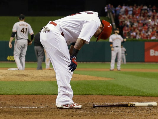 St. Louis Cardinals' Yadier Molina hunches over after hitting into a double play during the sixth inning in Game 2 of the National League baseball championship series against the San Francisco Giants Sunday, Oct. 12, 2014, in St. Louis. (AP Photo/David J. Phillip)