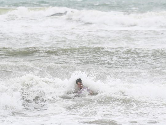 A lone swimmer braves the waves in Hollywood, Florida.