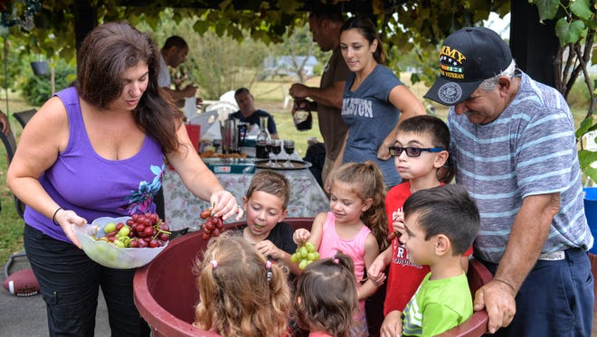 Members of the Chila family enjoy eating grapes while gathering for their annual tradition of homemade wine making in September in Mickleton.