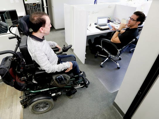 Miles Thornback, left, who has cerebral palsy, works