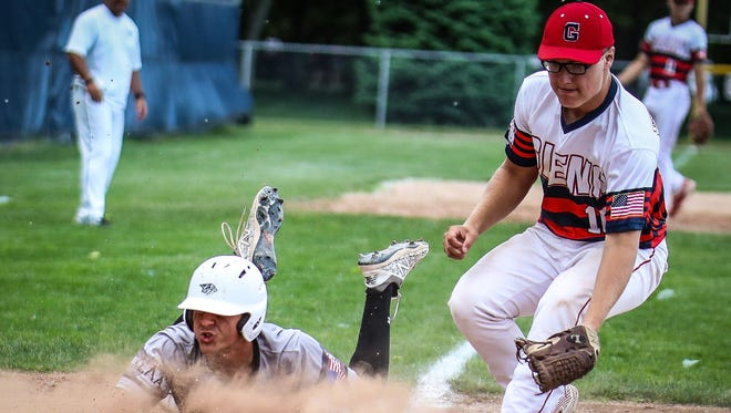 Plymouth's Evan Good (left) scores on a wild pitch as John Glenn pitcher Chad Stevens (right) covers the plate.