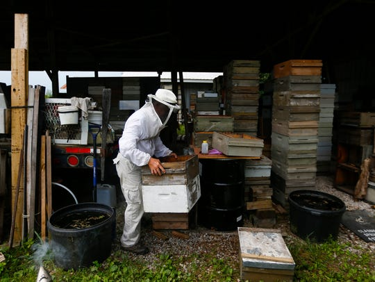 Beekeeper Michael Myer moves empty bee boxes to get