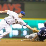 Jose Pirela (17) of the San Diego Padres is tagged out trying to steal second base by Milwaukee Brewers second baseman Aaron Hill during the seventh inning on Friday at Miller Park in Milwaukee.