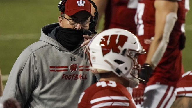 Wisconsin head coach Paul Chryst talks to players during the first half of an NCAA college football game against Illinois Friday, Oct. 23, 2020, in Madison, Wis.