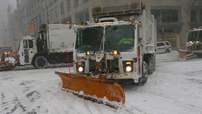 New York City Department of Sanitation snow plows shown clear the streets around Manhattan's Columbus Circle during Winter Storm Jonas.