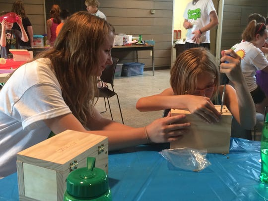 Emma Henjum, 9, of Suamico makes a wooden memory box with assistance from her Camp Lloyd buddy, Emily Carroll, in June 2015.