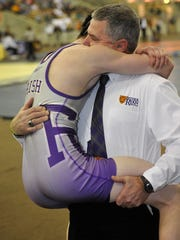 Kirby Simpson hugs his father, Father Ryan Coach Patrick Simpson, during the TSSAA state wrestling championships Feb. 14, 2015, at the Williamson County Expo Center in Franklin.