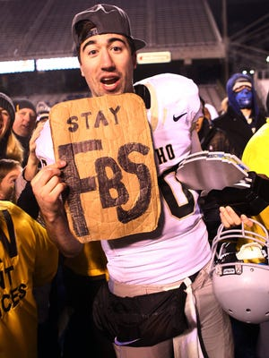 Idaho Vandals quarterback Matt Linehan (10) holds a sign supporting Idaho to stay in the FBS after the conclusion of the Idaho Potato Bowl held at Albersons Stadium. Idaho defeats Colorado State 61-50.