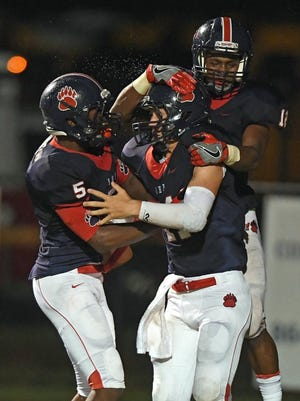 Bart Boatwright/Greenville News Belton-Honea Path quarterback Kameron Burton (11), center, celebrates with Xavier Nance (5), left, and O'Ryan Warren (12) after scoring on a 27-yard carry against Blue Ridge on Friday in Honea Path.