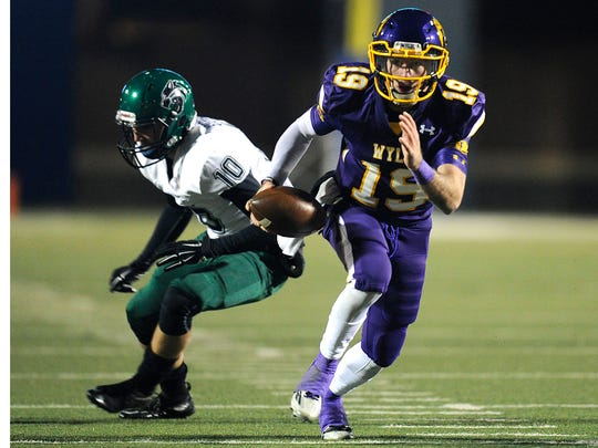 Wylie quarterback Zach Smith (19) slips past Kennedale linebacker Kade Stephenson (10) during the third quarter of the Bulldogs' 21-13 win in the Class 4A Div. I state semifinal playoff on Friday, Dec. 9, 2016, at Birdville Fine Arts/Athletics Complex.