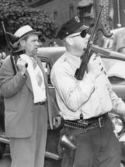 Two of the more than 50 Camden police officers who helped capture Howard Unruh. Detective William Kelley (left) and Officer Charles Hance hold their guns during the exchange of fire between officers and Unruh, who barricaded himself in his River Avenue apartment after the mass killing. Photo taken on Sept. 6, 1949 by Courier-Post staff