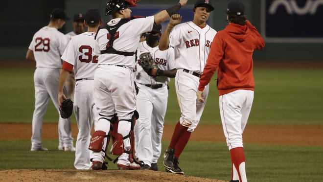 Boston Red Sox's Yairo Munoz, who had three hits in the game, is congratulated by teammates after their win over the Toronto Blue Jays in the second game of a baseball doubleheader Friday, Sept. 4, 2020, at Fenway Park in Boston.
