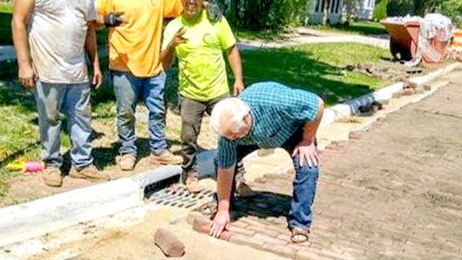 Harold Houser places the final brick onto the Pleasant Avenue surface as construction workers, who suggested Houser place the last brick to include him in the nostalgia, look on.