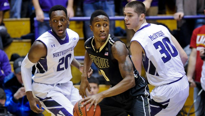 Purdue guard Jon Octeus (0) against Northwestern guard/forward Scottie Lindsey (20) and Northwestern guard Bryant McIntosh (30)  during the first half of an NCAA college basketball game  on Saturday, Jan. 31, 2015, in Evanston, Ill.