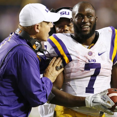 LSU Tigers head coach Les Miles hands  running back