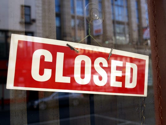 A red and white closed sign on a business window