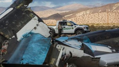Law enforcement officers keep watch on the wreckage near the site where a Virgin Galactic space tourism rocket, SpaceShipTwo, exploded and crashed in Mojave, Calif. on Nov 1. The explosion killed a pilot aboard and seriously injured another while scattering wreckage in Southern California's Mojave Desert, witnesses and officials said.