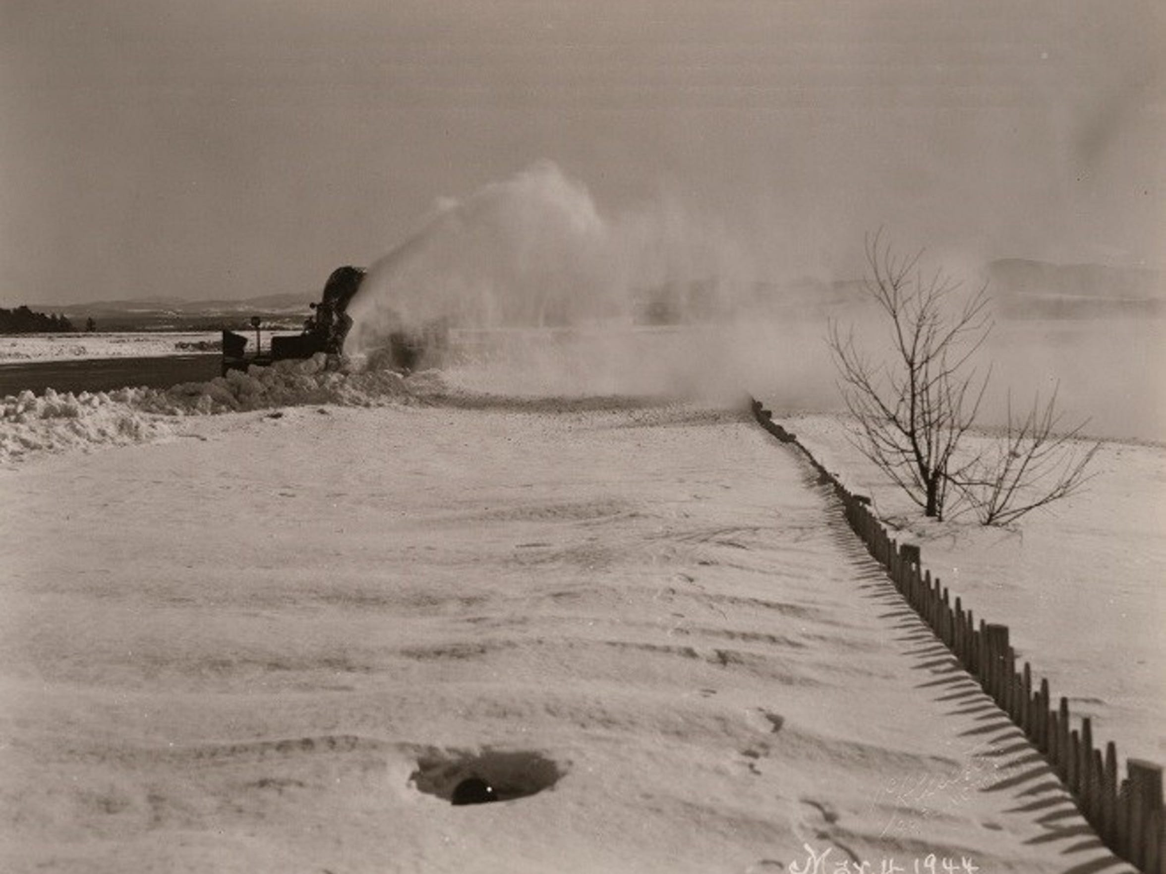 Rotary plow blows snow from a runway at the Burlington