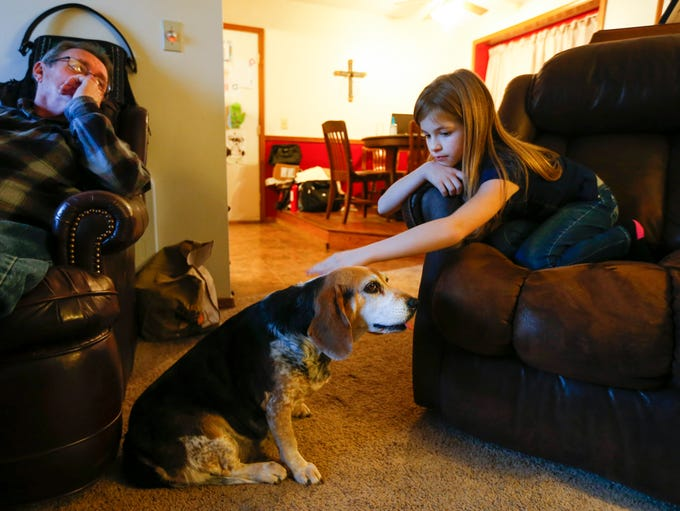 Eleven-year-old Lily Archer pets her beagle, Bella,