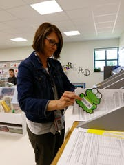 4K teacher Cindy Tatro prepares stuff for parents during