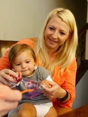 Pam Jinsky holds her 15-months-old daughter Pella's
