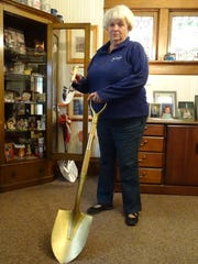 Deb Pinion, director of the Bucyrus Chamber of Commerce, holds the shovel Friday that she used to break ground in 2002 on the U.S. 30 route around Bucyrus. Pinion is retiring at the end of October after 21 years on the job.