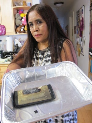 Dee Decasa holds her replacement Galaxy Note 7 smartphone in an aluminum pan at her home in Honolulu on Monday, Oct. 10, 2016, one day after the phone released smoke and sizzled. Samsung said it is halting sales of the Galaxy Note 7 after a spate of fires involving new devices that were supposed to be safe replacements for recalled models.