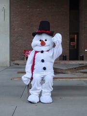 A snowman waves to children Friday before the Bucyrus