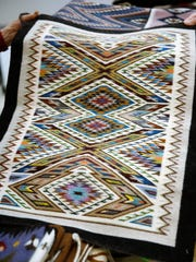 This Teec Nos Pos design weaving by Bessie Littleben which is included in the annual Navajo Benefit Rug Auction at the Farmington Museum at Gateway Park, features 93 shades.of color.