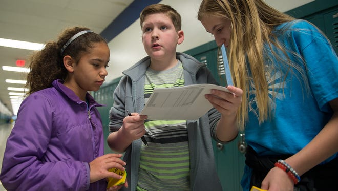 Desarie Bullock, left, William Hann and Jenna Plesz look at a list to see which lockers need Post-its.The notes are meant to encourage students taking part in PSSA testing.