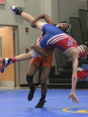 Mansfield Senior's Damoni Williams drops West Holmes' Walker Uhl during the Division II regional quarterfinals of the state dual team wrestling tournament at Ontario High School.
