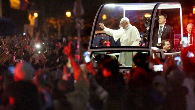Pope Francis waves from the popemobile as he greets some of the thousands of people who went to see him and take part in the Festival of Families on Sept. 26 in Philadelphia.