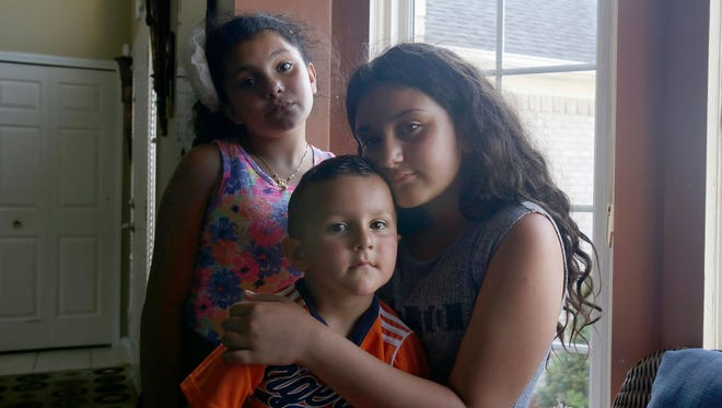 From clockwise, siblings Meryana Butris, 9, Lilly Butris, 12, and Eli Butris, 3, at their Sterling Heights, Mich., home June 12, 2017. Their father, Joe Butris, was picked up by Immigration and Customs Enforcement and detained June 11, 2017.