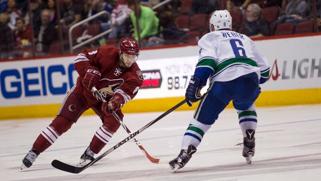 Coyotes right wing Tobias Rieder takes the puck up against Canucks defenseman Yannick Weber at a Coyotes home game March 22, 2015 at Gila River Arena in Glendale, Arizona.