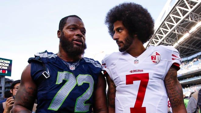 San Francisco 49ers quarterback Colin Kaepernick (7) and Seattle Seahawks defensive end Michael Bennett (72) talk following a 37-18 Seattle victory at CenturyLink Field.