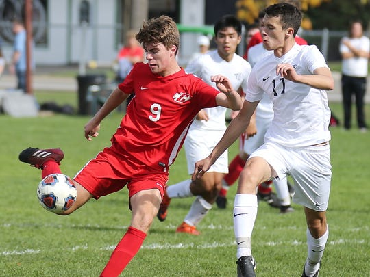 Canton's Avery Olson (9) puts a foot into the ball. At right for Plymouth is Alex Bowser (17).