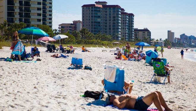 Public beachgoers enjoy the sun as Moraya Bay Beach Tower chairs sit out in the private beach area in the distance on Wednesday, Jan. 24, 2018, in North Naples.