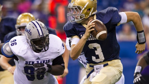 Indianapolis Cathedral High School's Collin Barthel scrambles away from Ben Davis High School's Norman Oglesby during first half action of the Horseshoe Classic at Lucas Oil Stadium in Indianapolis Friday, August 23, 2013. / Doug McSchooler/for The Star