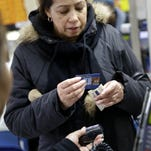 A woman pays for her groceries using a food stamp program at a supermarket in West New York, N.J.,  Jan. 12. Many middle class families, affected by the increasing cost of living, are turning to food stamp programs.