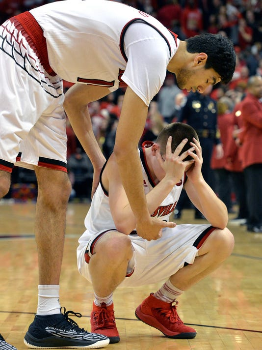 Louisville forward Anas Mahmoud (14), top, consoles guard Ryan McMahon (30) following their loss to Virginia in an NCAA college basketball game, Thursday, March 1, 2018, in Louisville, Ky. (AP Photo/Timothy D. Easley)