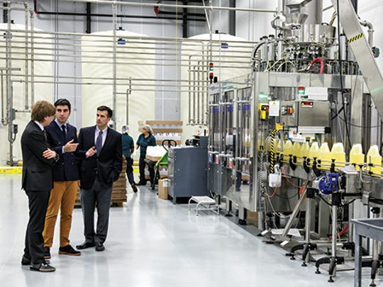 Colavita executives view a phase of the blending and bottling process.