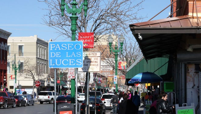 A Paseo De Las Luces sign near some of the green lamp posts along S. El Paso street Thursday.