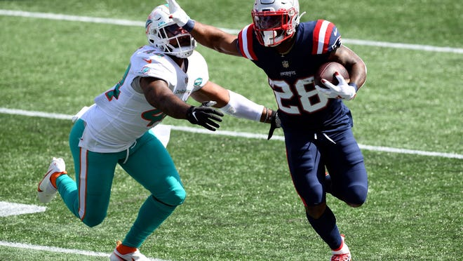 New England Patriots running back James White (28) rushes against Miami Dolphins cornerback Byron Jones (24) during the second quarter at Gillette Stadium.