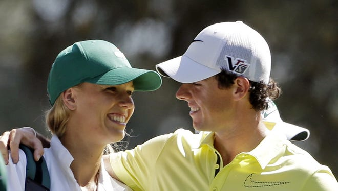 """Pro golfer Rory McIlroy hugs his caddie, tennis player Caroline Wozniacki, during the par-3 competition before the Masters golf tournament in April. The couple announced their engagement Tuesday.   AP FILE - In this April 10, 2013, file photo, Rory McIlroy, of Northern Ireland, hugs his caddie, tennis player Caroline Wozniacki, during the par-3 competition before the Masters golf tournament in Augusta, Ga. One of the top power couples in sports announced their engagement on Twitter. A spokesman for McIlroy confirmed that he popped the question in Sydney, where Wozniacki is starting to prepare for the Australian Open in Melbourne. McIlroy tweeted, """"Happy New Year everyone! I have a feeling it's going to be a great year!! My first victory of 2014."""" He added a hash tag, """"She said yes!!"""" (AP Photo/Darron Cummings, File)"""