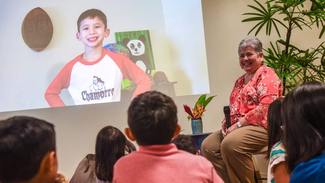"Frank Thomas ""Kiko"" Freitas Guzman addresses young audience members through a prerecorded video message as he and his grand-aunt Laura Torres Souder Introduce the children's storybook ""Kiko's Adventure on the Magic Flying Proa"" during a launch or the book at the Guam Museum in Hagåtna on Saturday, Nov. 25, 2017."
